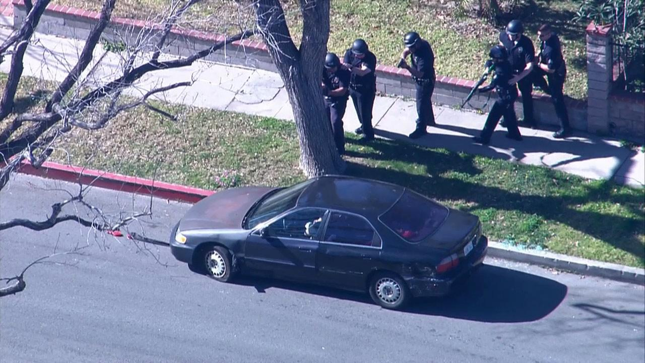 Police officers cautiously approach a vehicle at the end of a pursuit in Panorama City on Friday, Feb. 1, 2013. The suspect sat in his car and inhaled nitrous oxide from balloons.