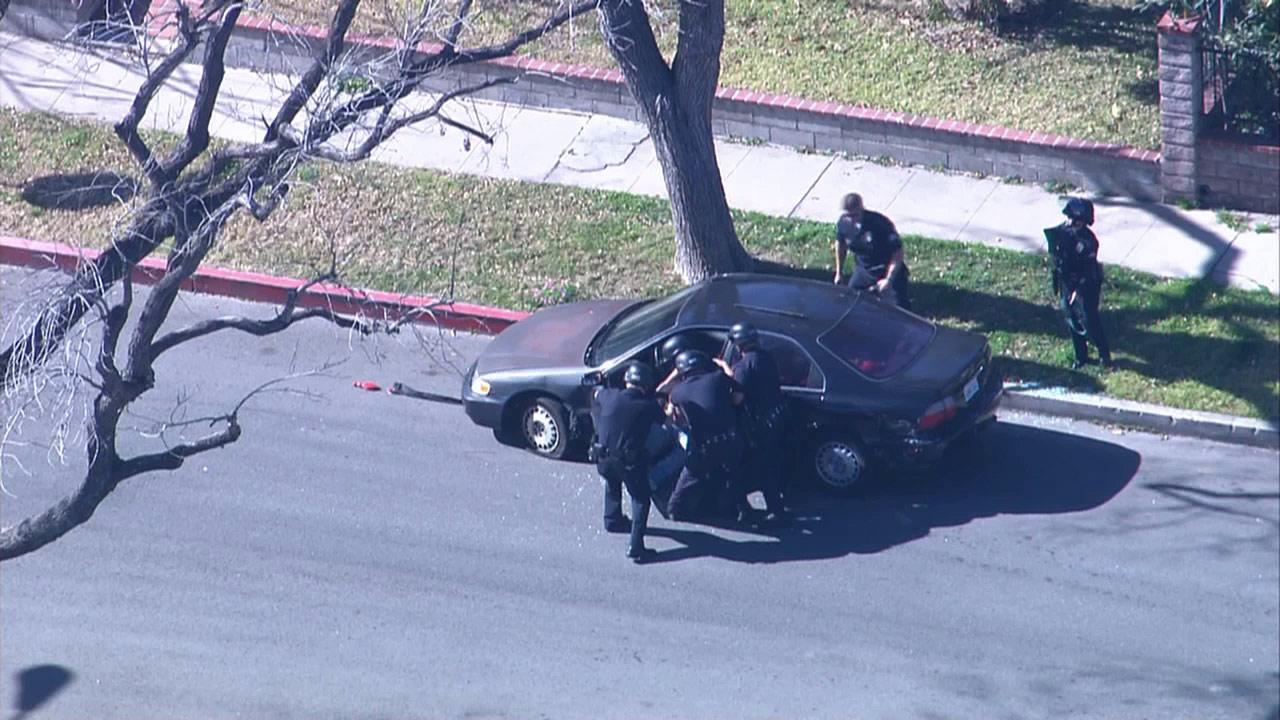 Police officers forcefully pull a suspect out of his vehicle at the end of a pursuit in Panorama City on Friday, Feb. 1, 2013. The suspect sat in his car and inhaled nitrous oxide from balloons.