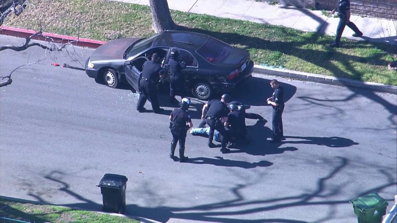 Police officers forcefully pulled a suspect out of his vehicle at the end of a pursuit in Panorama City on Friday, Feb. 1, 2013. The suspect sat in his car and inhaled nitrous oxide from balloons.