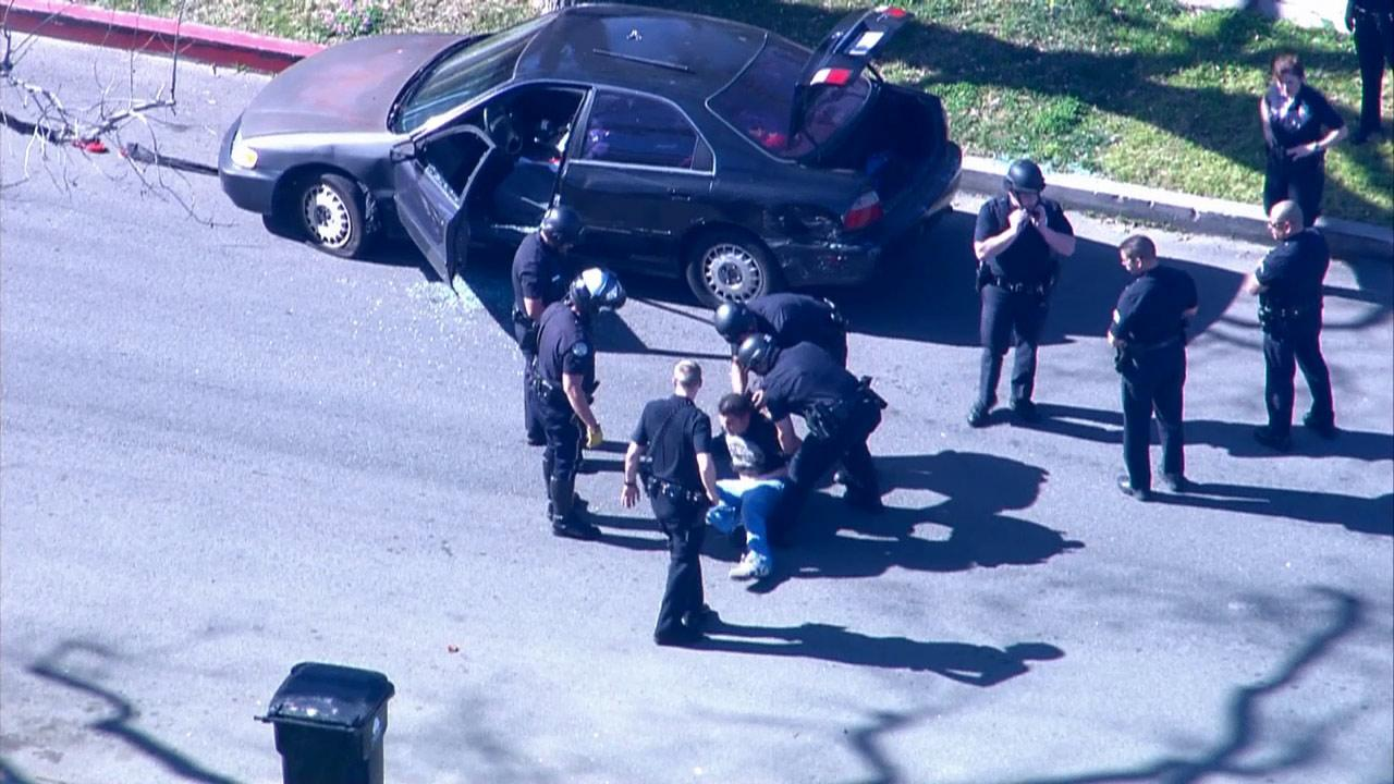 A chase suspect is taken into custody at the end of a pursuit in Panorama City on Friday, Feb. 1, 2013. The suspect had been sitting in his car, inhaling nitrous oxide from balloons.