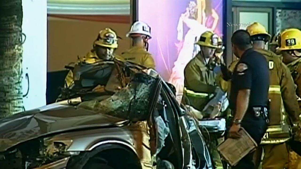 Firefighters are seen at the scene of a crash on Van Nuys Boulevard in Van Nuys that killed a female passenger and hospitalized the driver on Saturday, Feb. 16, 2013. Officials said alcohol and high speeds are to blame.
