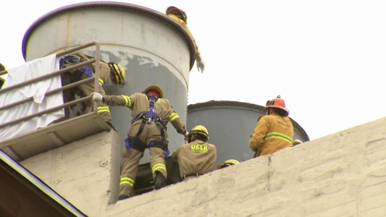 Investigators are seen on the roof of the Cecil Hotel, where a body was found on Tuesday, Feb. 19, 2013.