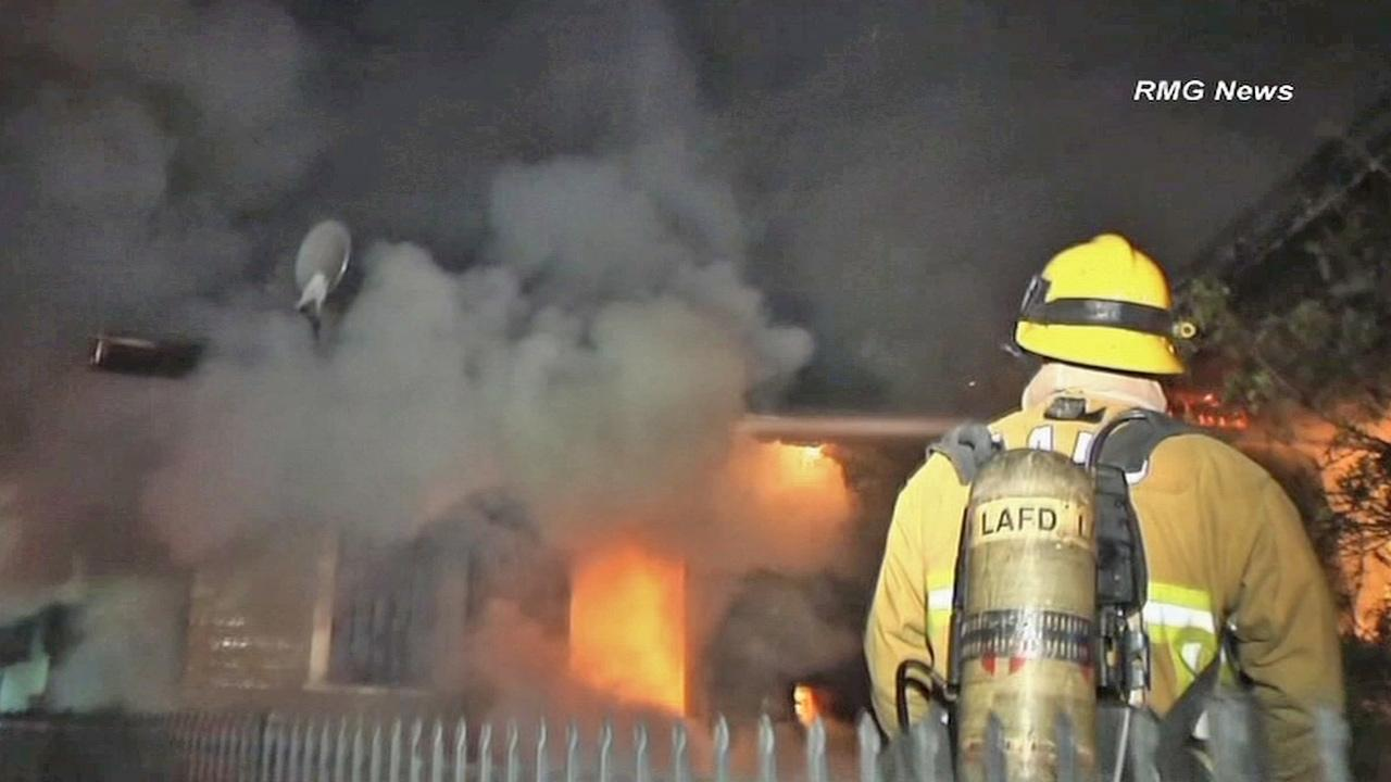 A firefighter works to put out a house fire in the 1900 block of Scott Avenue in Echo Park on Thursday, March 28, 2013.