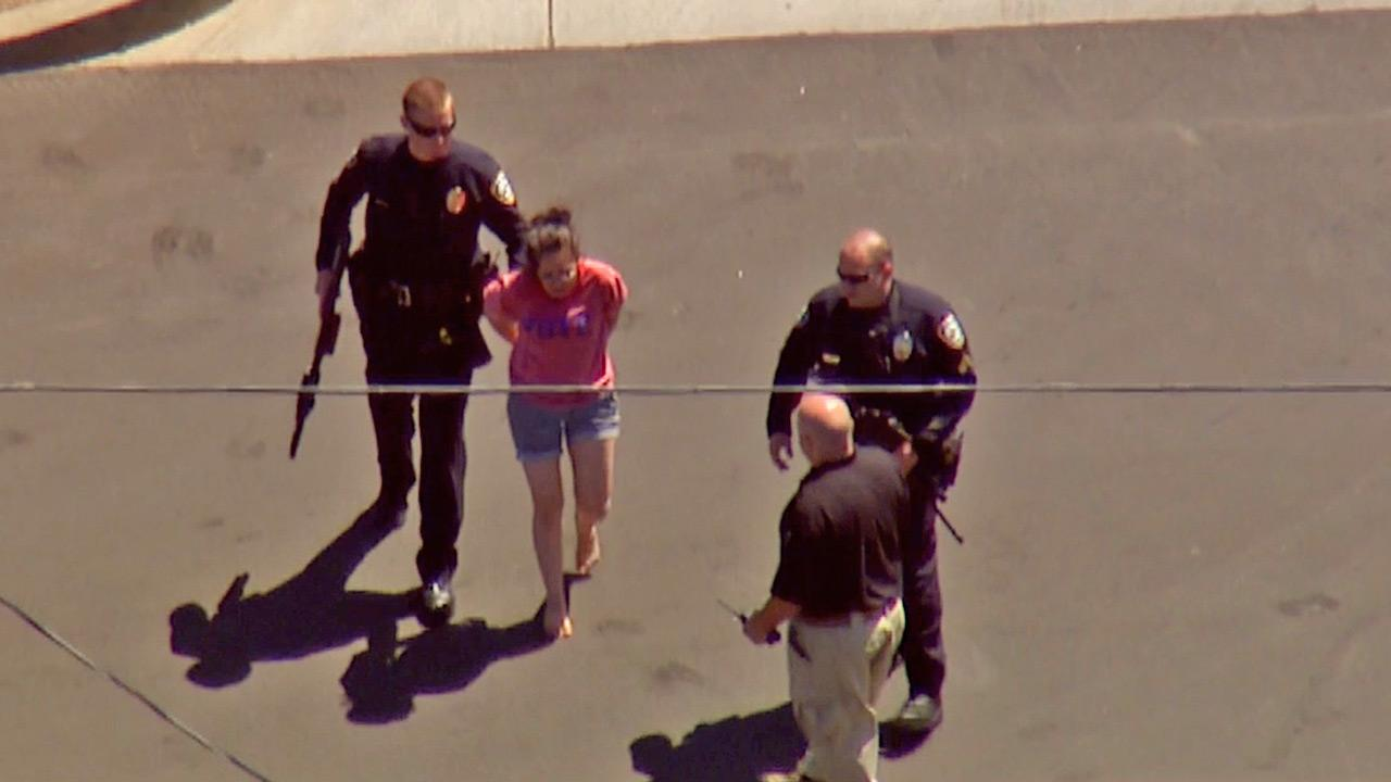 An armed female suspect is taken into custody after a standoff at an El Segundo business on Tuesday, April 16, 2013.