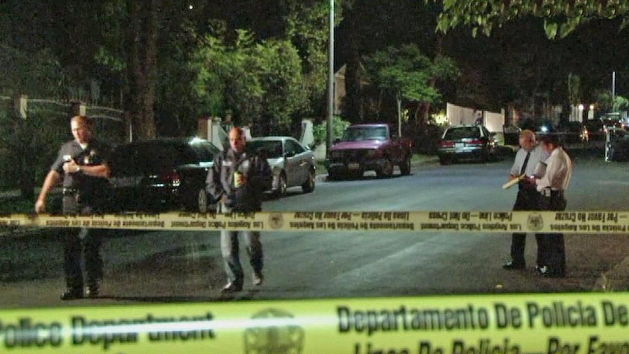 Los Angeles investigators are shown behind crime scene tape following an officer-involved shooting in Lake View Terrace on Friday, May 17, 2013.