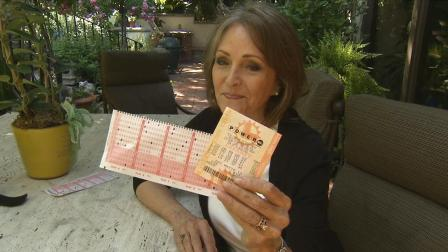 Margit Arrobio of Pasadena holds up Powerball tickets, one of which had all six winning numbers for the drawing on Wednesday, May 15, 2013, but were purchased an hour late.