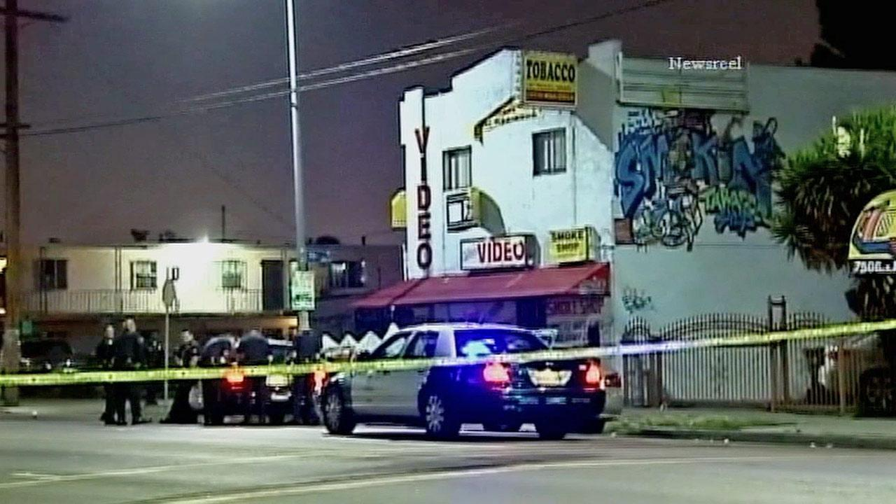 Law enforcement officials are shown behind crime tape at a scene of a deadly drive-by shooting in the 7500 block of South Main Street in South Los Angeles on Thursday, May 23, 2013.k