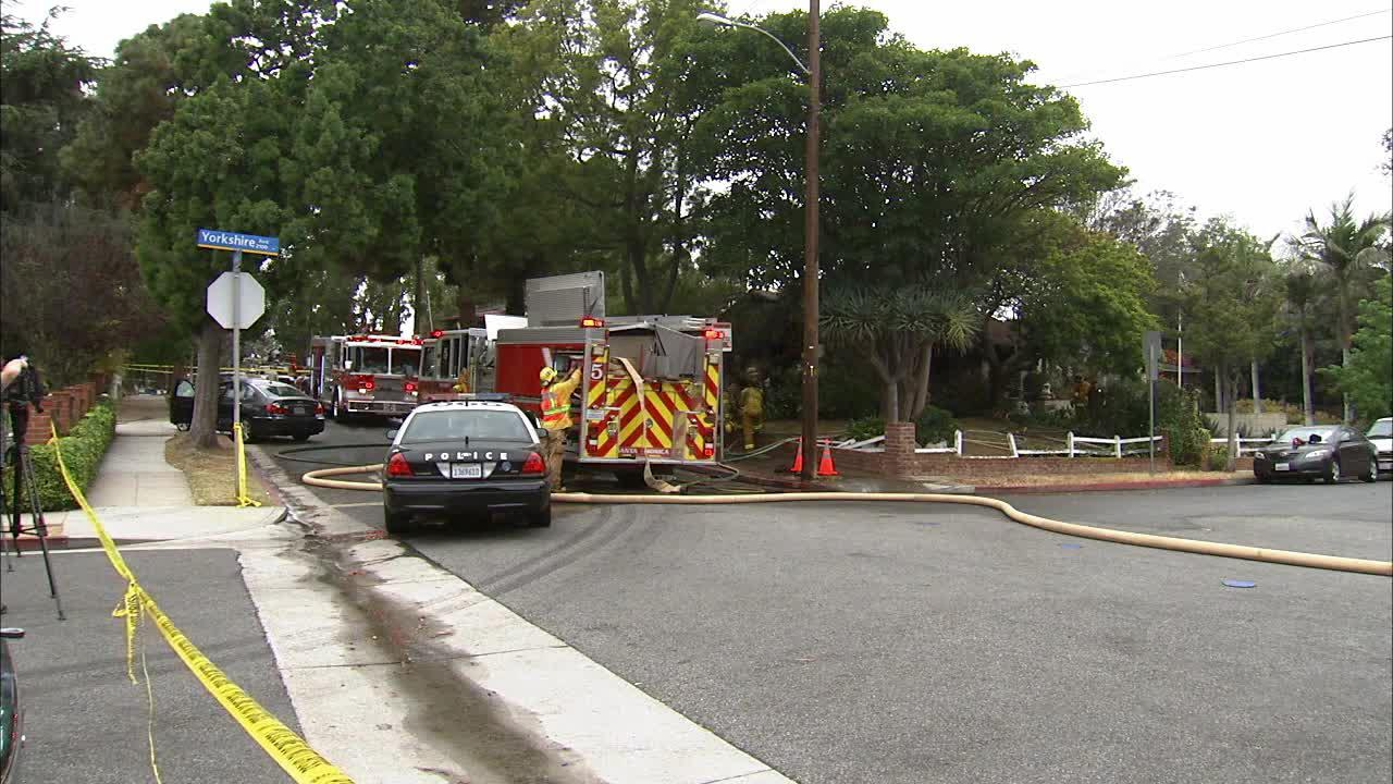 Firefighters appear outside a home that burned in the 2000 block of Yorkshire Avenue in Santa Monica on Friday, June 07, 2013. The home was one of multiple investigation scenes.