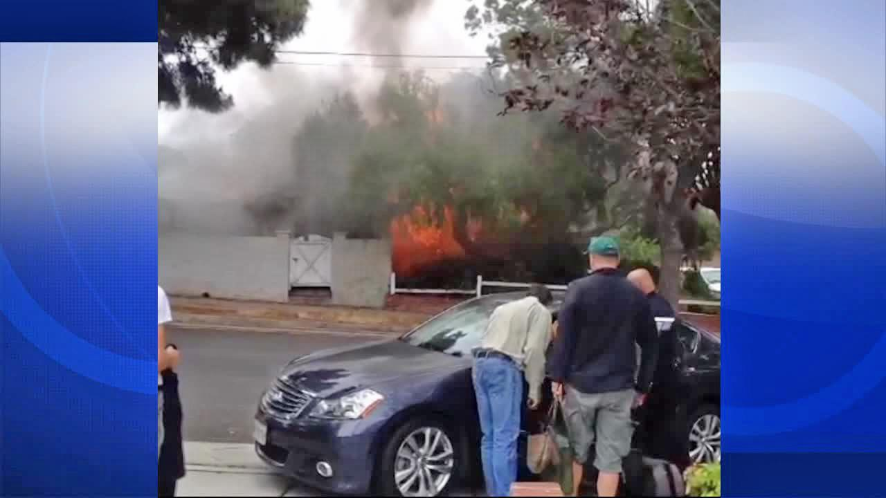Bystanders look on as a house is engulfed in flames in the 2000 block of Yorkshire Avenue in Santa Monica on Friday, June 07, 2013. The home was one of multiple investigation scenes connected to a shooting rampage, resulting in at least five deaths.