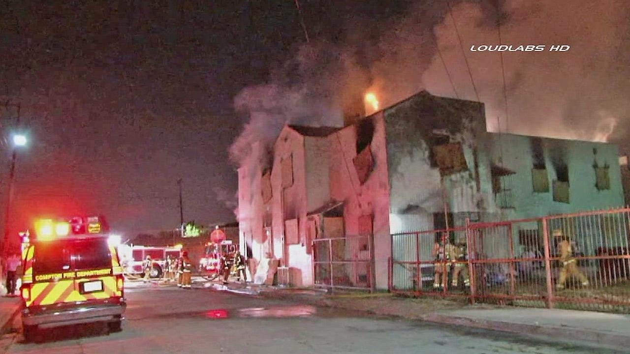 Firefighters work to put out a fire in a burning building in Compton Monday, June 10, 2013.