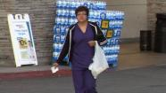 A shopper walks out of a Los Angeles-area grocery store holding a single-use plastic bag.