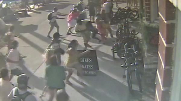Pedestrians run out of the way of an oncoming car on the Venice Beach boardwalk Saturday, Aug.