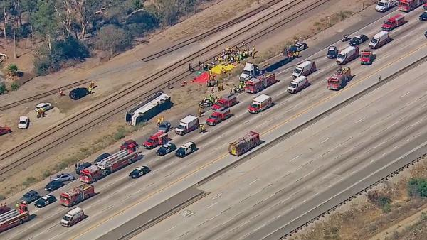 Emergency officials help victims who were injured in a tour bus crash on the eastbound 210 Freeway in Irwindale on Thursd