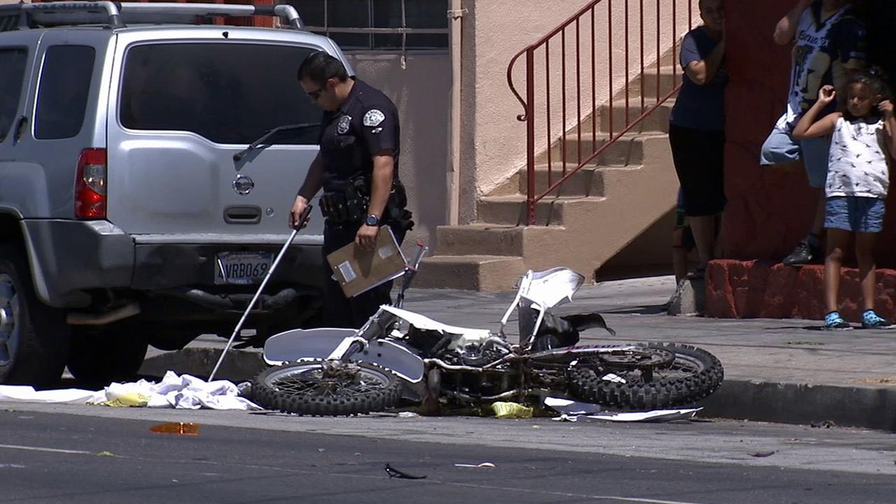 A police officer combs through evidence after a traffic collision on the 400 block of East Colden Avenue in South Los Angeles on Sunday, Sept. 1, 2013.