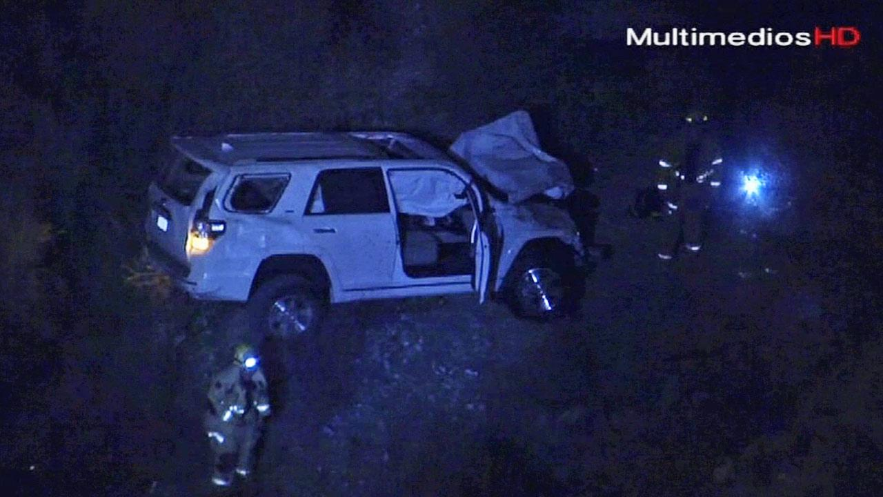 A wrecked white SUV is shown at the bottom of an embankment of Shinn Road in the Angeles National Forest on Tuesday, Sept. 24, 2013.