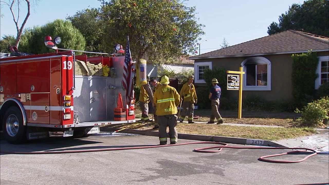 Firefighters battle a fire at a home in the 2400 block of Roswell Avenue in Long Beach Sunday, Sept. 29, 2013.