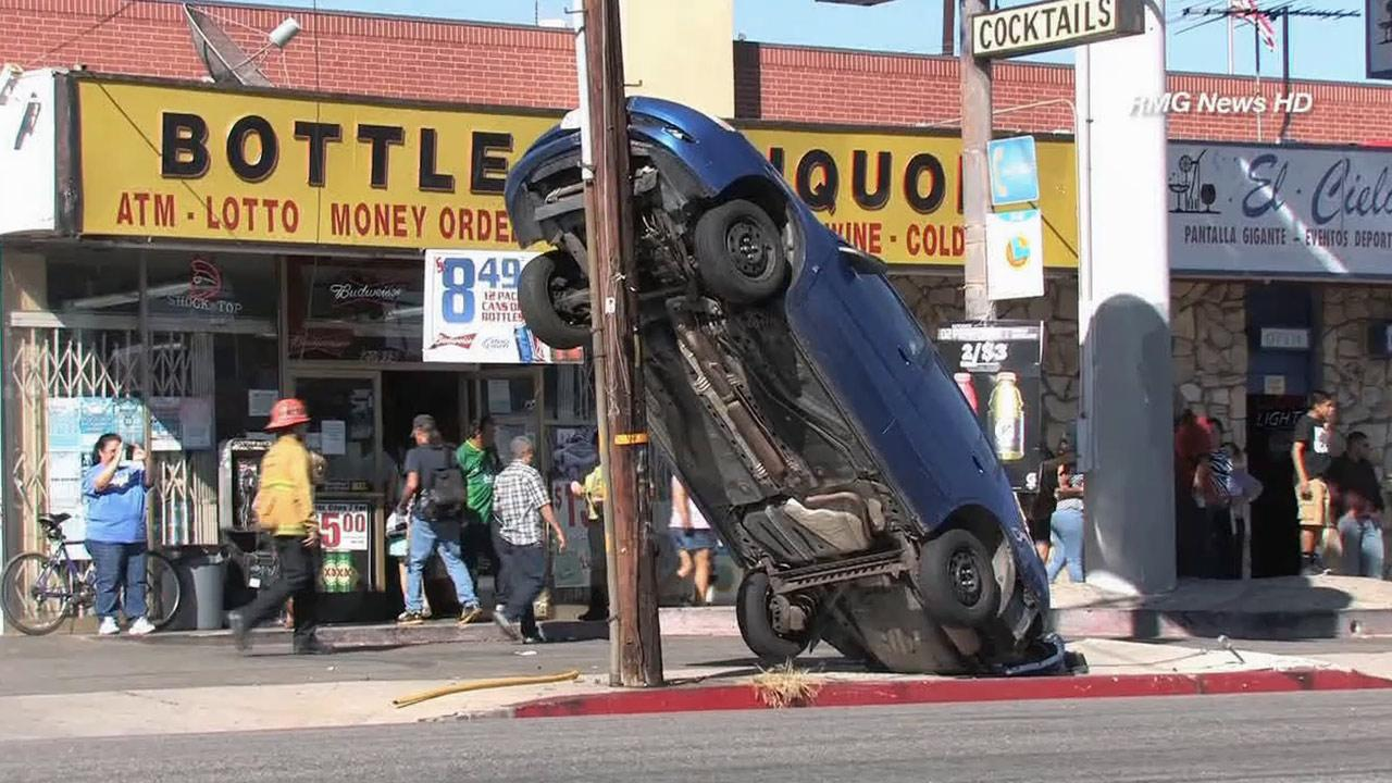 A car rests nearly upright on a power pole after crashing near De Soto Avenue and Vanowen Street in Canoga Park on Sunday, Sept. 29, 2013.