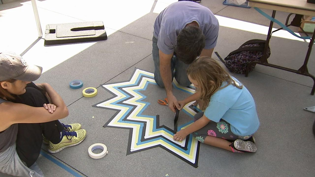 Artists use tape to make a design on the floor at a Big Draw L.A. event in downtown Los Angeles on Sunday, Oct. 13, 2013.