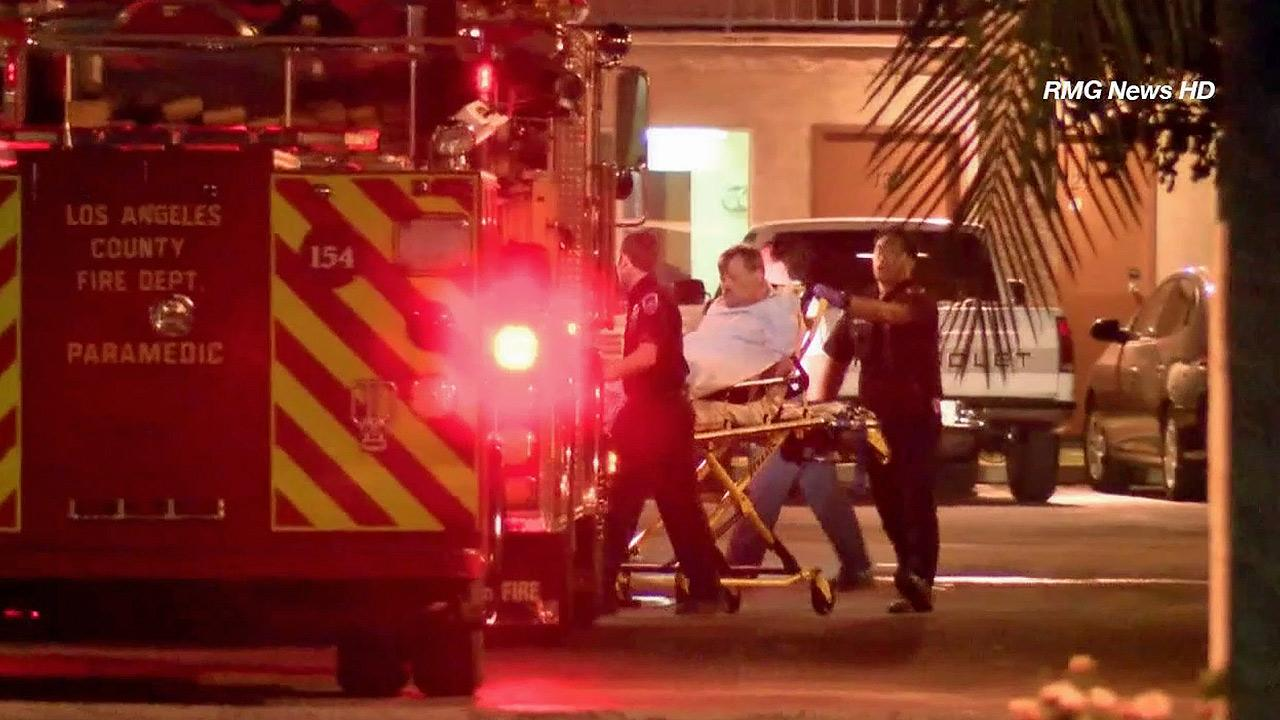 A male suspect is seen being put into an ambulance following a standoff with police at the Arrow Inn Motel in the 400 block of East Arrow Highway in Azusa on Saturday, Oct. 19, 2013.