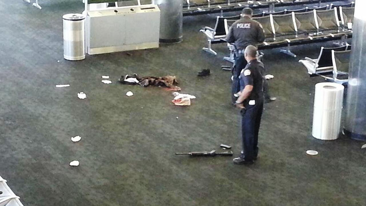 Police officers stand near an unidentified weapon after a shooting in Terminal 3 of the Los Angeles International Airport on Friday, Nov. 1, 2013.