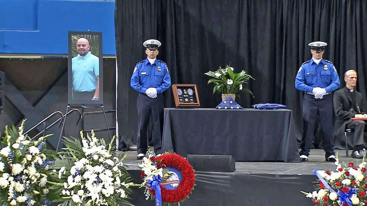 Two TSA officers stand near a framed photo of murdered TSA Officer Gerardo Hernandez at the slain officers public memorial service on Tuesday, Nov. 12, 2013.