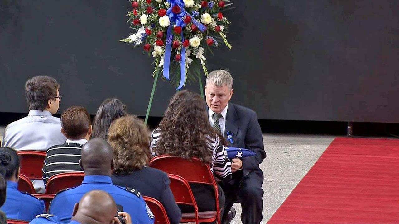 Acting Secretary of Homeland Security Rand Beers presents a folded American flag to the wife of TSA officer Gerardo Hernandez at the slain officers public memorial service on Tuesday, Nov. 12, 2013.