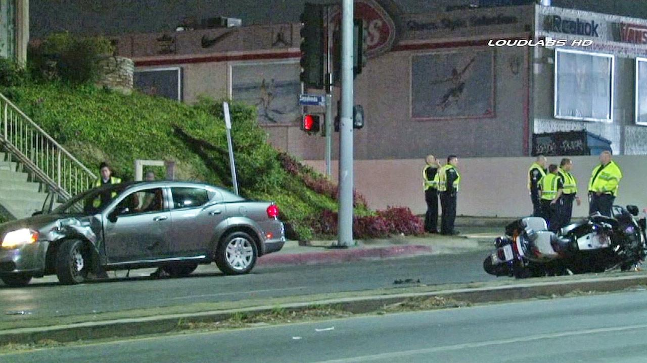 Police officers investigate the scene of a car crash involving a Los Angeles Police Department motorcycle officer in Van Nuys on Saturday, Jan. 11, 2014.
