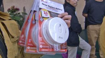 A firefighter holds up smoke detectors during a campaign to prevent fire-related deaths.