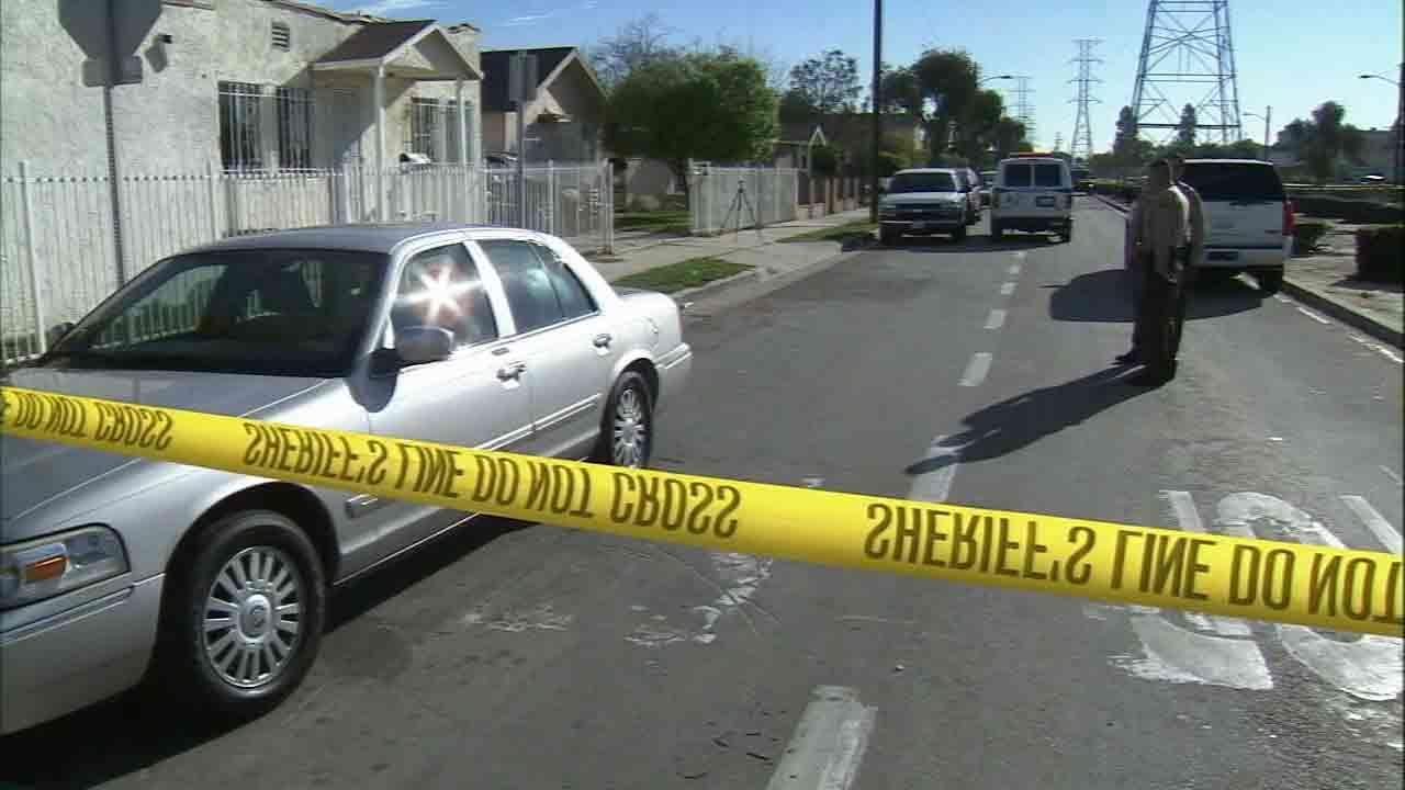 Deputies respond to the scene of a homicide on West 98th Street in the Westmont area of Los Angeles Sunday, March 9, 2014.