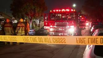 Firefighters tape off an area where a converted garage in Los Angeles went up in flames on Wednesday, April 16, 2014.