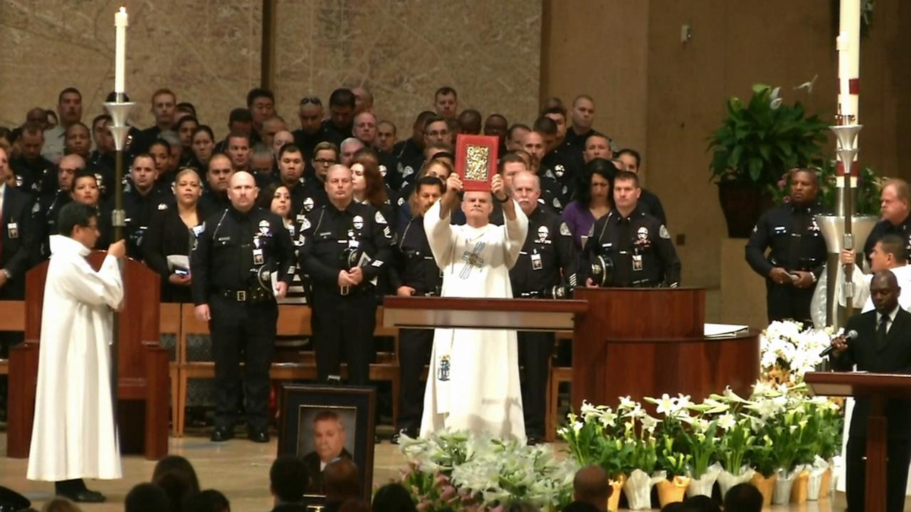 Hymns are sung while mourners honor the life of LAPD Officer Chris Cortijo during his funeral on Tuesday, April 22, 2014.