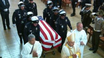 Uniformed officers carry Chris Cortijos casket out of the church to be taken to his final resting place at Forest Lawn Hollywood Hills.