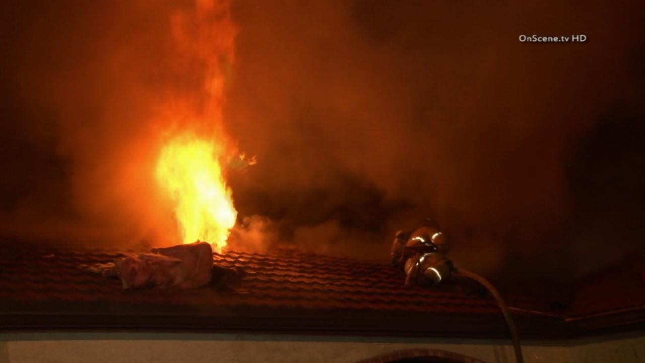 A firefighter pushes back on a house fire in Anaheim on Wednesday, April 23, 2014.