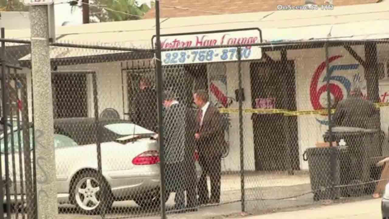 Los Angeles police respond to the scene of a fatal armed robbery at Western Hair Lounge on the 6500 block of South Western Avenue Friday, April 25, 2014.