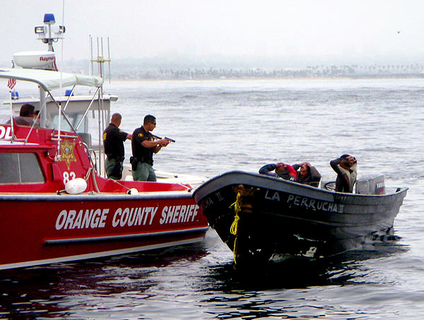 Deputies with the Orange County Sheriff's Department hold three suspects at gunpoint about one mile off the Newport Beach coastline on Sunday, August 7, 2011.