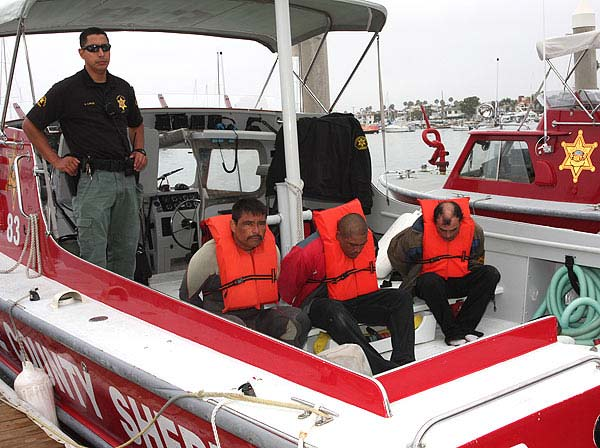 A deputy with the Orange County Sheriff&#39;s Department stands guard over three Mexican nationals arrested on Sunday, August 7, 2011 on charges of drug possession, suspected smuggling activity and illegally attempting to enter the United States. Authorities said the men traveled from Mexico to Orange County for a drug-smuggling run in a 25-foot panga. <span class=meta>(Orange County Sheriff&#39;s Department Deputy William Nelson)</span>