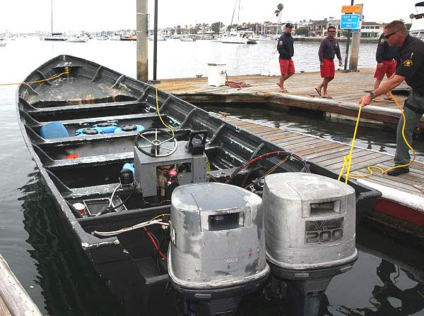 A deputy with the Orange County Sheriff&#39;s Department secures a small boat to the docks in front of the Harbor Patrol station on Sunday, August 7, 2011. Authorities arrested three men aboard the 25-foot panga off Newport Beach in what may have been a drug-smuggling run. <span class=meta>(Orange County Sheriff&#39;s Department Deputy William Nelson)</span>