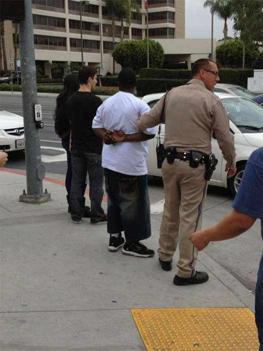 A man is seen being apprehended by authorities at the California State University Fullerton campus during a search for two possibly armed suspec
