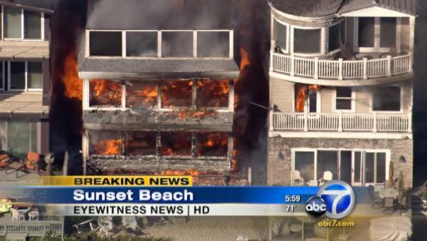 A four-alarm fire destroyed one beachfront home and damaged two others in the Sunset Beach on Thursday, May 12, 2011.