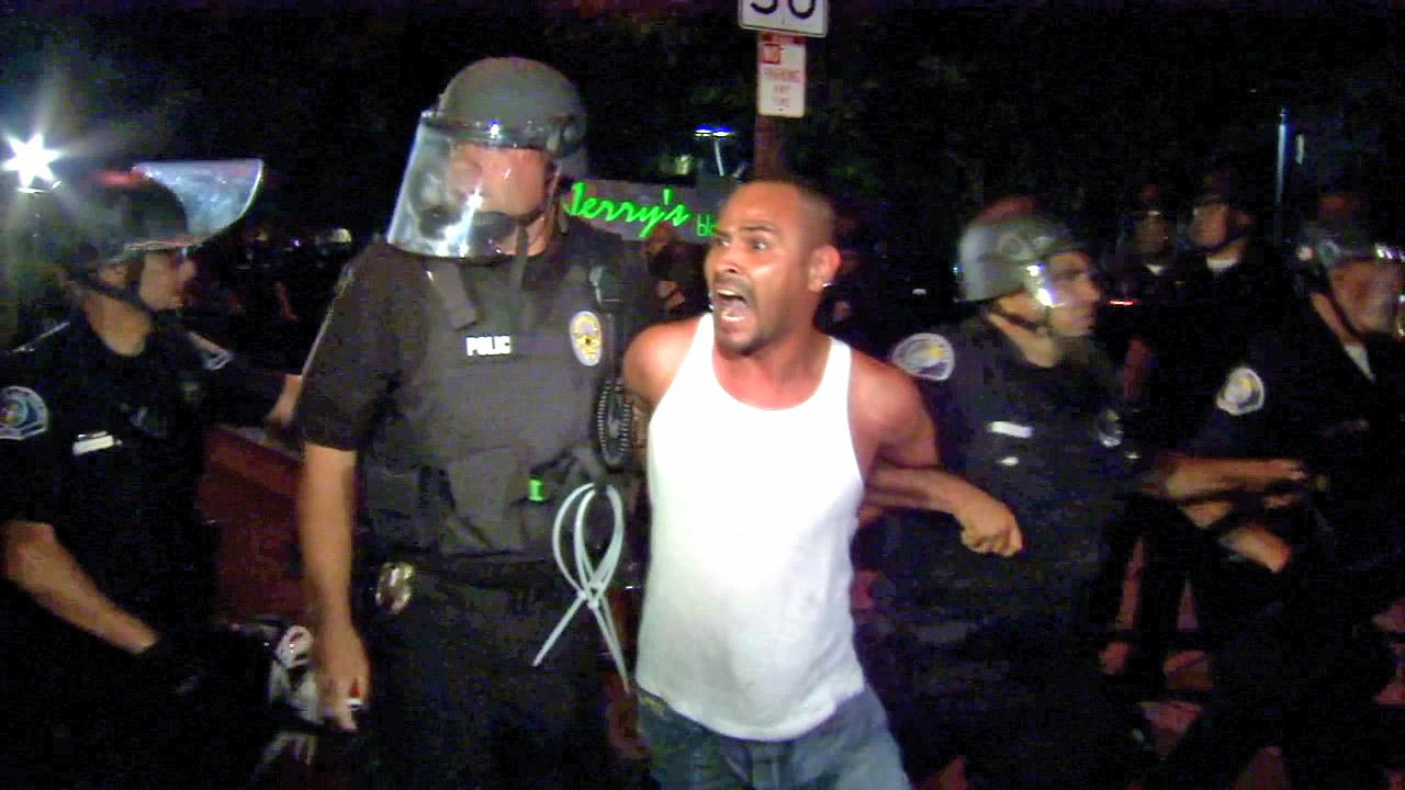A man is handcuffed by police officers during a protest that turned violent on Tuesday, July 24, 2012, over two recent fatal shootings by police in Anaheim