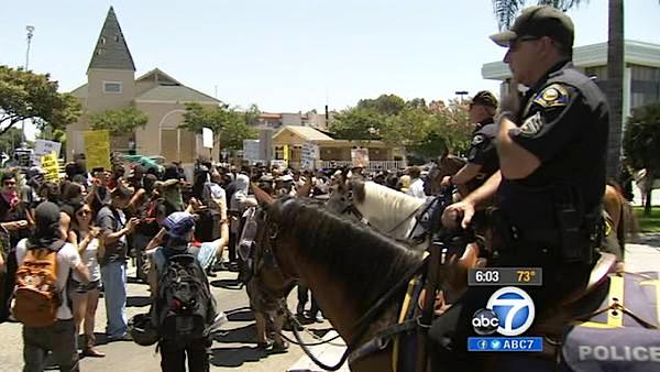 Officers on horseback keep a watchful eye on protesters demonstrating in