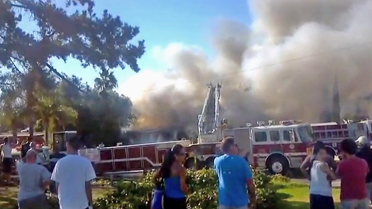 A still from amateur video shows smoke from a house fire in Buena Park on Sunday, Sept. 16, 2012. A driver who passed by the blaze ran inside the home and rescued an 80-year-old woman from the flames.