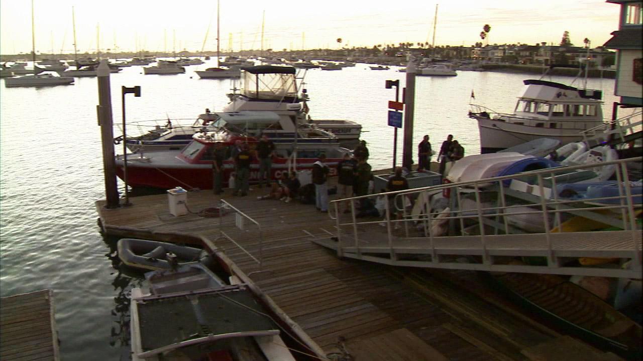 Law enforcement officials are seen in Newport Beach, where 15 suspected illegal immigrants were discovered on board a cabin cruiser on Thursday, Oct. 18, 2012.