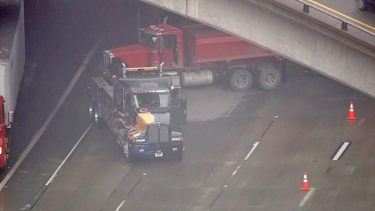 A tow truck is seen after it jackknifed and spilled gravel across lanes on the 91 Freeway in Anaheim on Monday, Dec. 3, 2012.