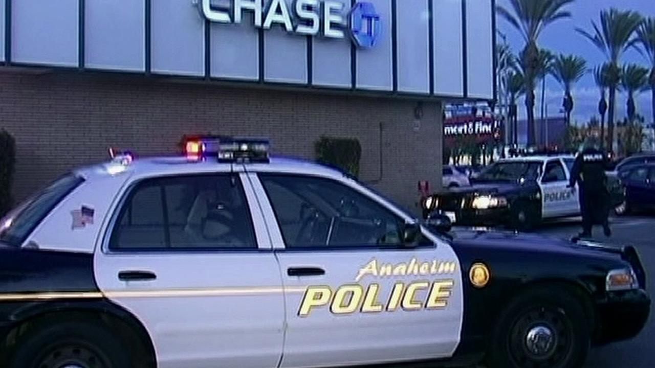 Anaheim police are seen at a parking lot for a Chase bank, where a woman was attacked with a hammer on Tuesday, Dec. 18, 2012.
