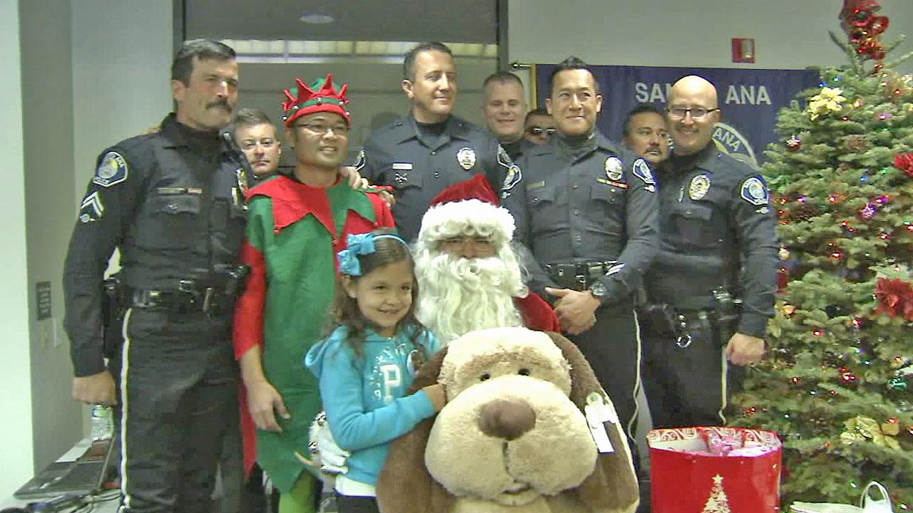 Grecia Meza (center) is seen with members of the Santa Ana Police Foundation after they worked with the Spark of Love Toy Drive to give her toys for Christmas.