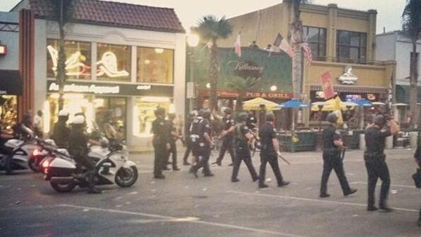 A heavy police presence is seen during what police called a major disturbance in Huntington Beach following the U.S.