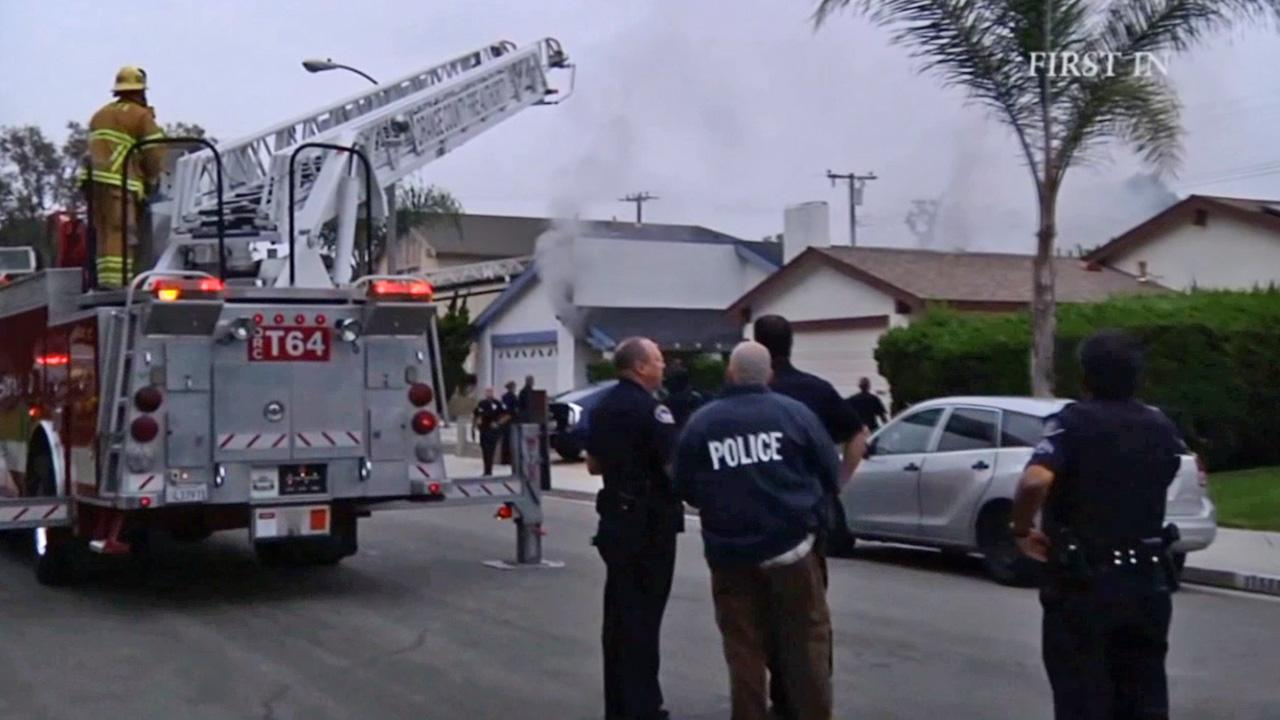 Firefighters and police respond to a fire at a home on the 11500 block of Panay Street in Cypress on Saturday, Aug. 3, 2013.