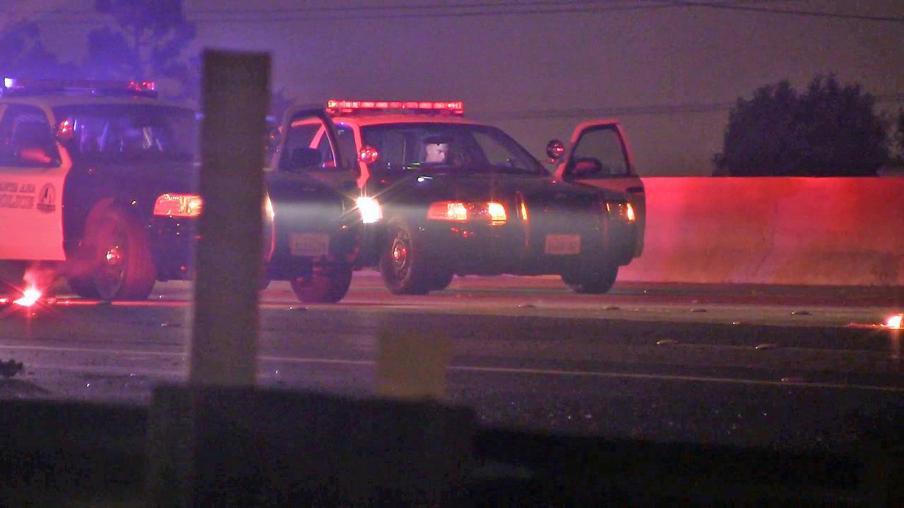 Police are seen on the 55 Freeway in Santa Ana after a man ran across lanes of the freeway on Sunday, Aug. 25, 2013.