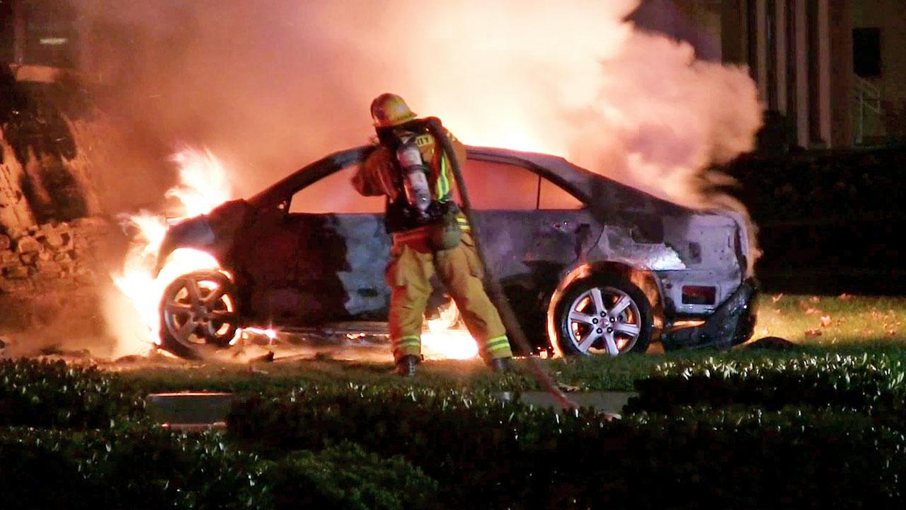 A firefighter douses a car engulfed in fire following a crash on Katella Avenue in the city of Orange on Saturday, Aug. 31, 2013.